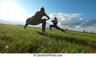 Young female acrobat workout on the grass at summer sunset,...