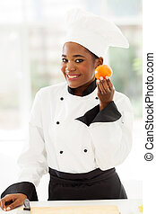 young female african chef holding tomato
