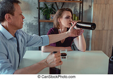 Young female alcoholic drinking wine from the bottle