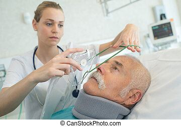young female anesthetist putting oxygen mask on senior patient