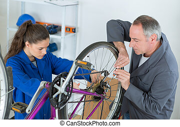 young female apprentice aligning bike tires