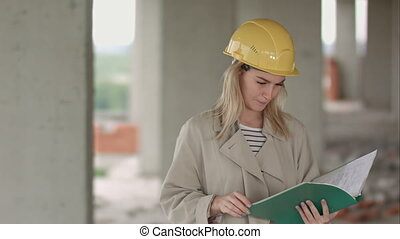 Young female architect construction engineer at a construction site eximaining documents