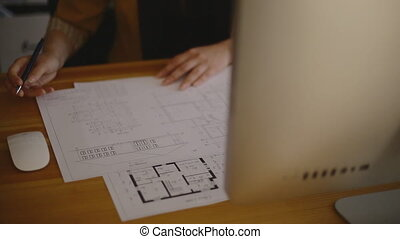 Young Female Architect Studying Plans In Office on blueprint.