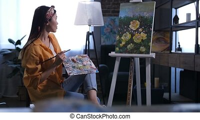 Young female artist admiring her finished painting - Side...