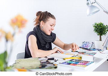 Young female artist drawing sketch using sketchbook