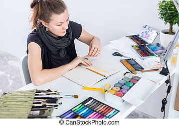 Young female artist drawing sketch using sketchbook with pencil at her workplace in studio. Side view portrait of inspired painter.