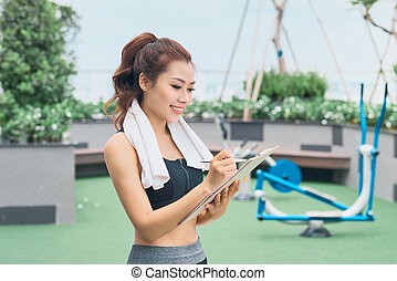 Young female asian trainer taking notes outdoors