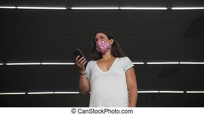 Low angle shot of young beautiful woman wearing pattern covid-19 protection face mask standing at metro subway and browsing smartphone