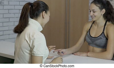 Young female at reception desk in sports club.