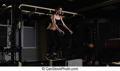 young female athlete doing a box jump at the gym - focus on...