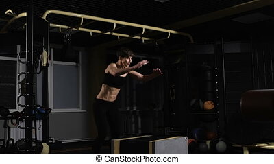 young female athlete doing a box jump at the gym - focus on the woman
