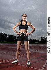 Young female athlete on athletics running track