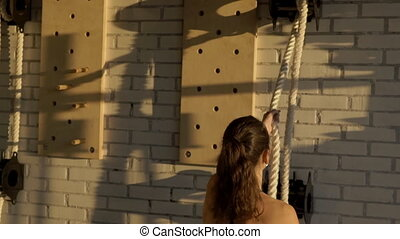 Young female athlete pulls rope in sports club. Woman stands...