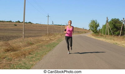 Young female athlete runner jogging during outdoor workout