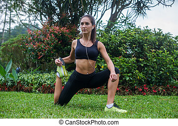 Young female athlete stretching her legs on grass, warming-up before running. Fitness instructor doing exercises in park wearing headphones.