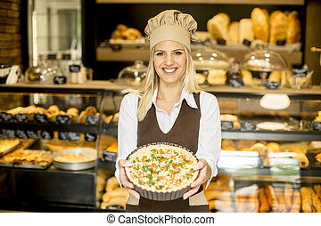 Young female baker standing in the bakery and shows pizza