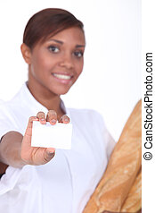 Young female baker with a blank business card