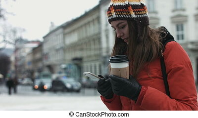 Young female being waiting for her friends outdoors and using smartphone to text. Girl is receiving a message on her mobile device.
