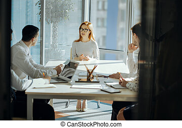 Young female boss having meeting with employees