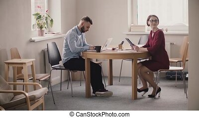 Young female boss sits by the table across male employee...