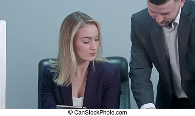Young female boss sitting at workplace and reading paper with caucasian colleague in office