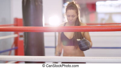 Young female boxer resting with her arms on the ring ropes