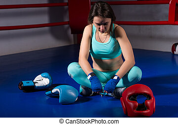 Young female boxer sitting near lying boxing gloves and helmet