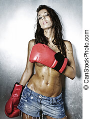 Young female boxer topless in jeans and boxing gloves