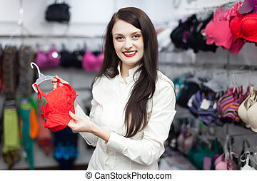 female buyer choosing bra at clothing shop - Young female ...