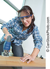young female carpenter using machine in the workshop