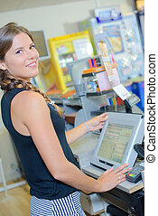 young female cashier operating at the cash desk in store