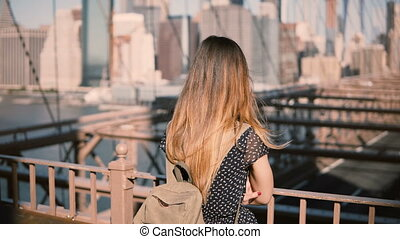 Young female Caucasian tourist in stylish sunglasses with backpack standing alone at Brooklyn Bridge, New York City 4K.