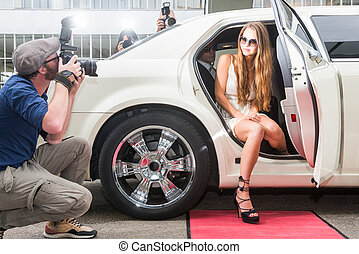 Young female celebrity posing in limousine for paparazzi on red carpet