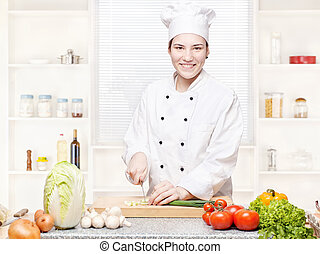 female chef cutting onions on the cutting board in kitchen