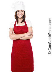 Young female chef with folded arms