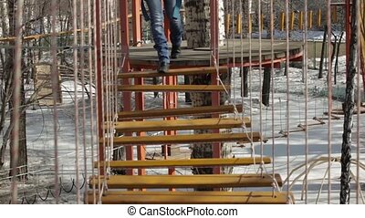 Young female climber walks by pendant log bridge on high ropes course in extreme park