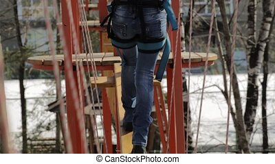 Young female climber walks by pendant log bridge on high...