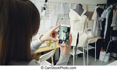 Young female clothing design blogger is shooting tailoring...