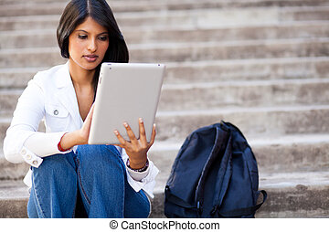 college student using tablet computer outdoors - young...
