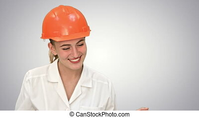 Young female construction engineer smiling while have a video conference with laptop on white background.
