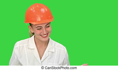 Young female construction engineer smiling while have a video conference with laptop on a Green Screen, Chroma Key.