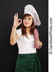 Young female cooking chef showing OK sign