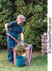 Young female cutting branch for composting
