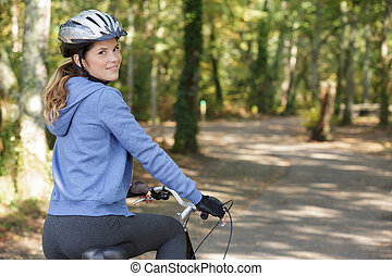 young female cyclist in the forest