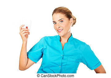 Young female dentist holding tooth model
