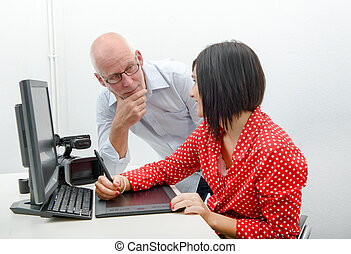 Young female designer and her boss using graphics tablet