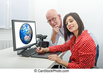 Young female designer and mature man using graphics tablet