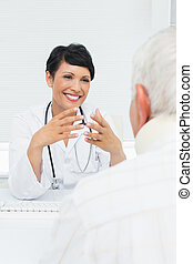 Young female doctor attentively listening to senior patient...