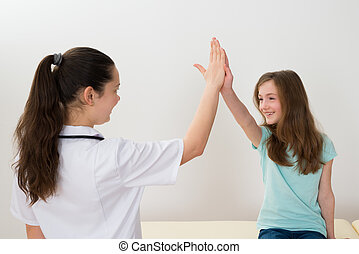 Doctor Giving High Five To Girl