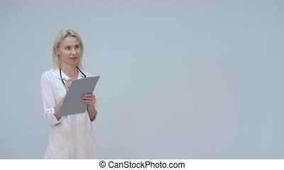 Young female doctor in white room writing